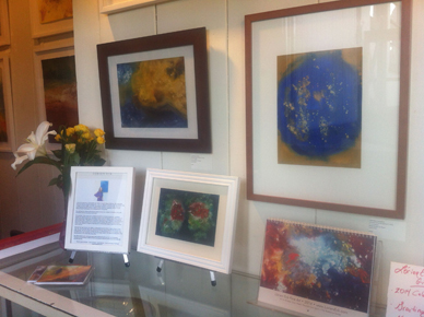 image of cosmic heart nebula painting hanging on wall with lorien's paintings